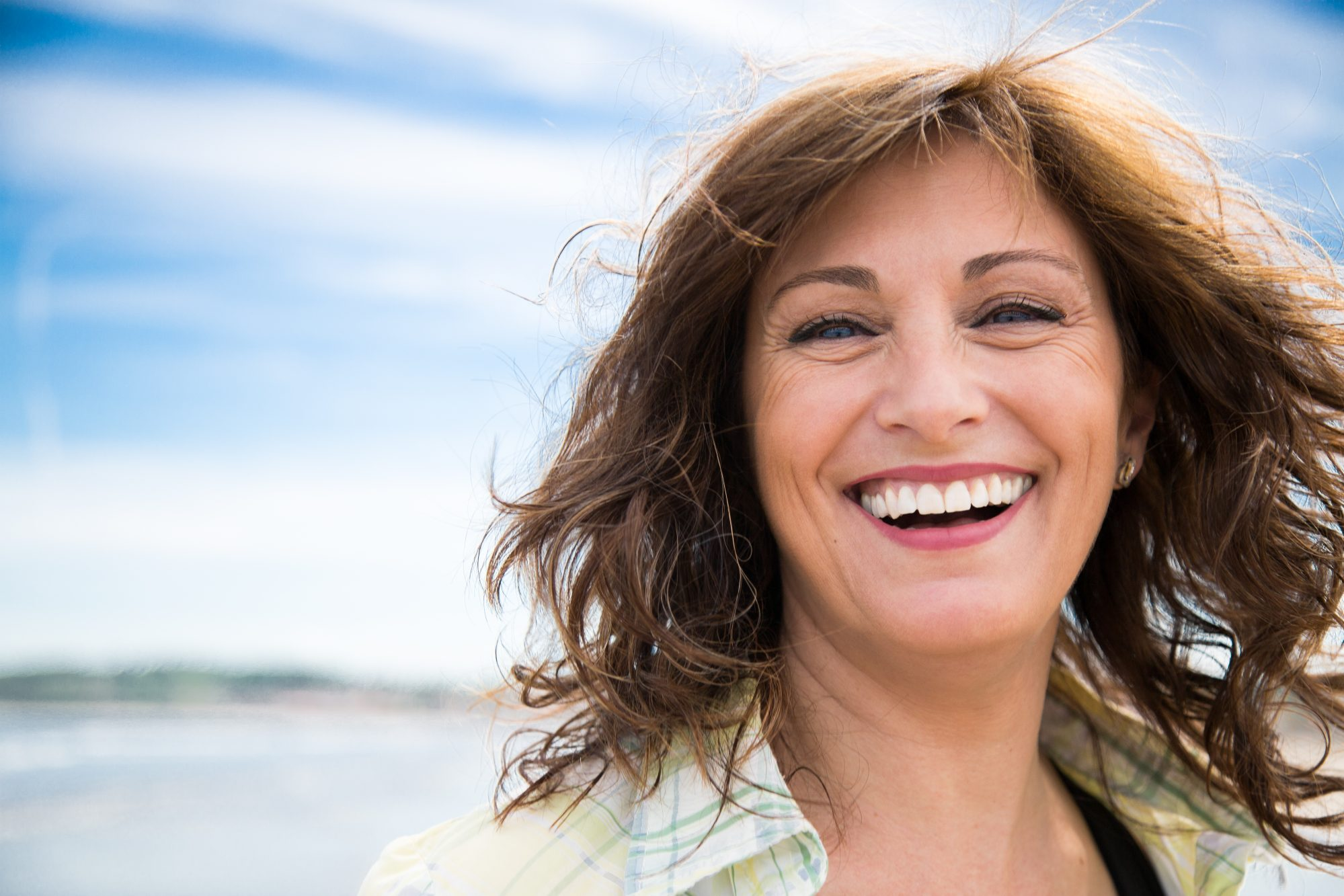 Happy woman with bladder leakage laughing on the beach