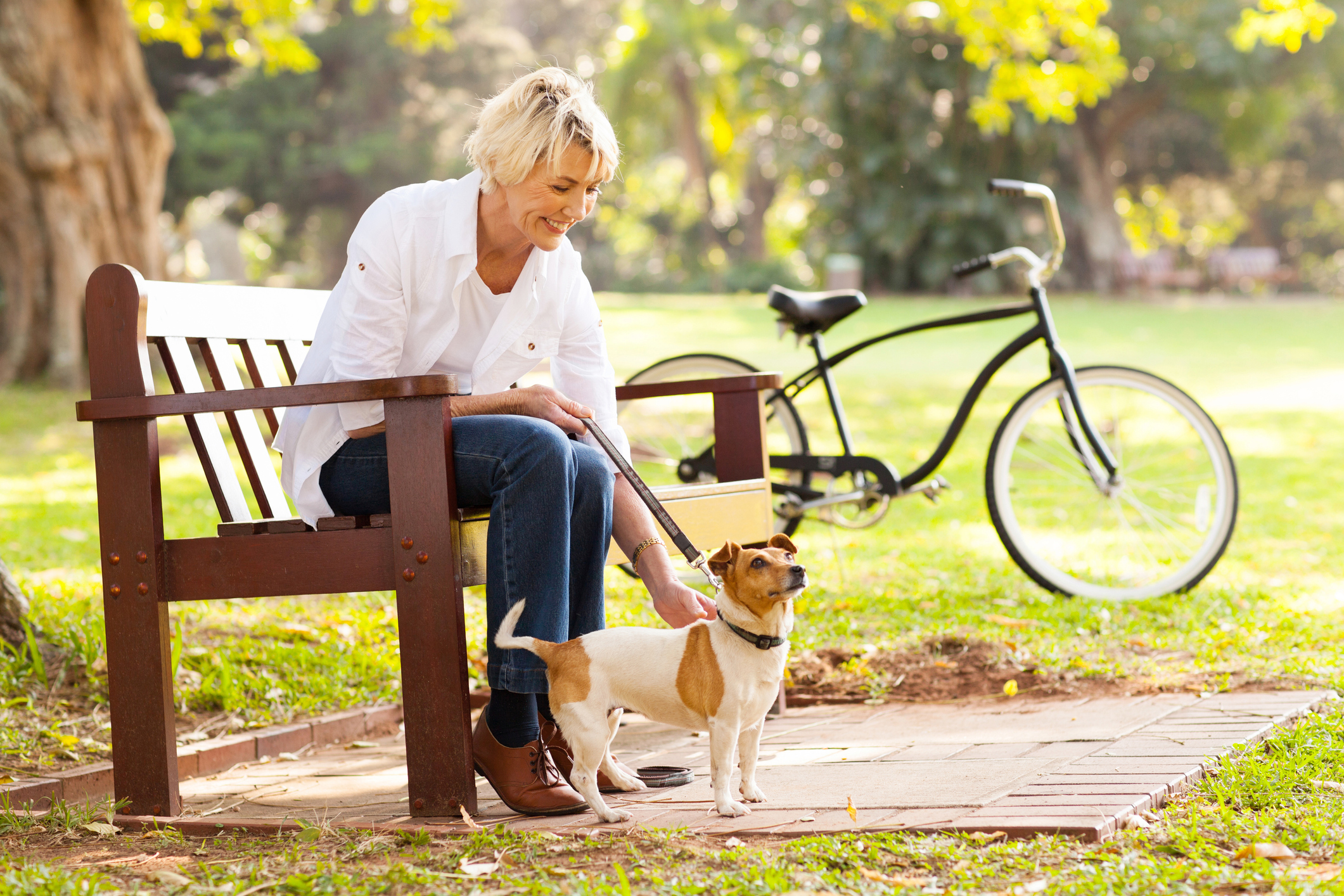 woman with incontinence on bench with dog