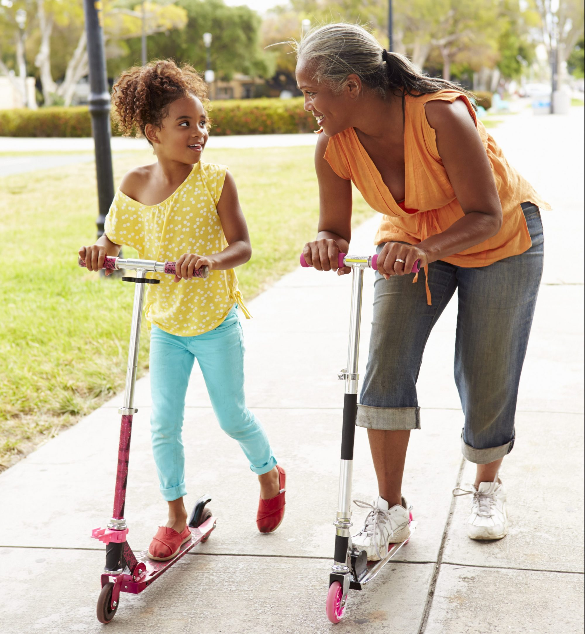 Grandmother And Granddaughter Riding Scooters In Park